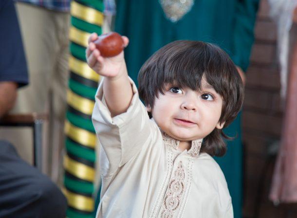 Cute boy holding up a gulab jamun, South Asian dessert.
