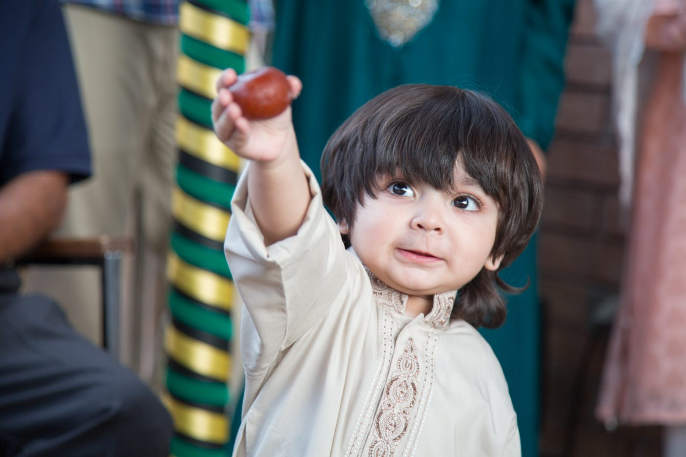 Cute boy holding up a gulab jamun, South Asian dessert.