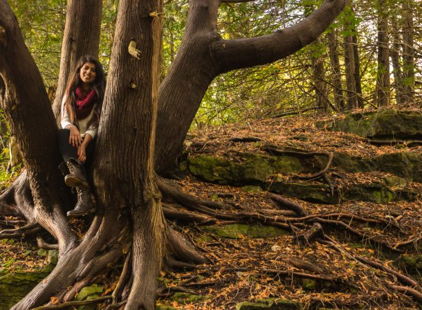Girl sitting in tree in the forest.