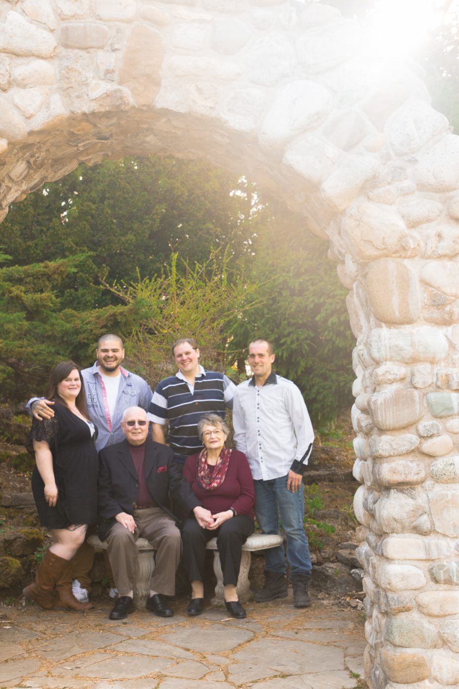 Family photo shoot in the sun under a stone arch.