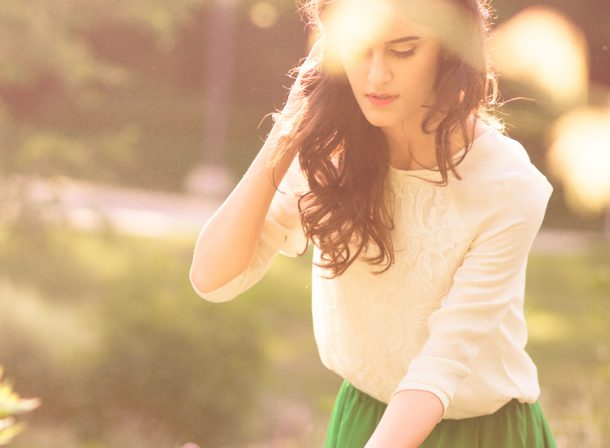 Girl in green skirt and white shirt picking flowers in sunlight.