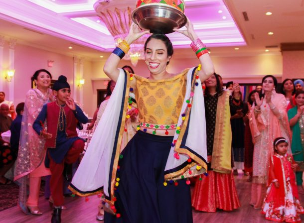 South Asian girl dancing in Jaago ceremony.
