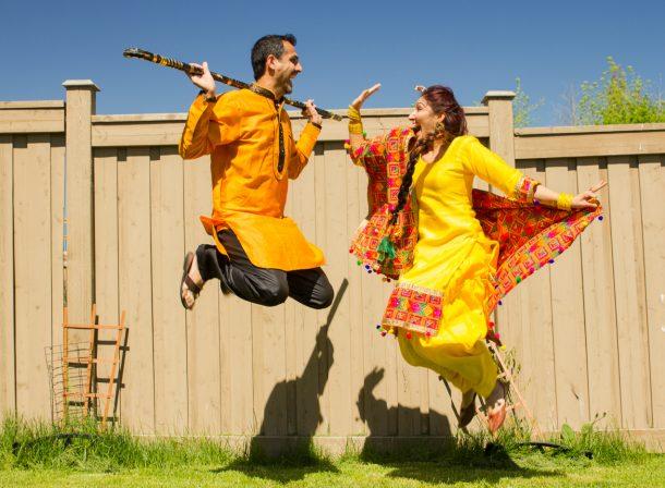 Punjabi dressed couple jumping in bhangra dance.