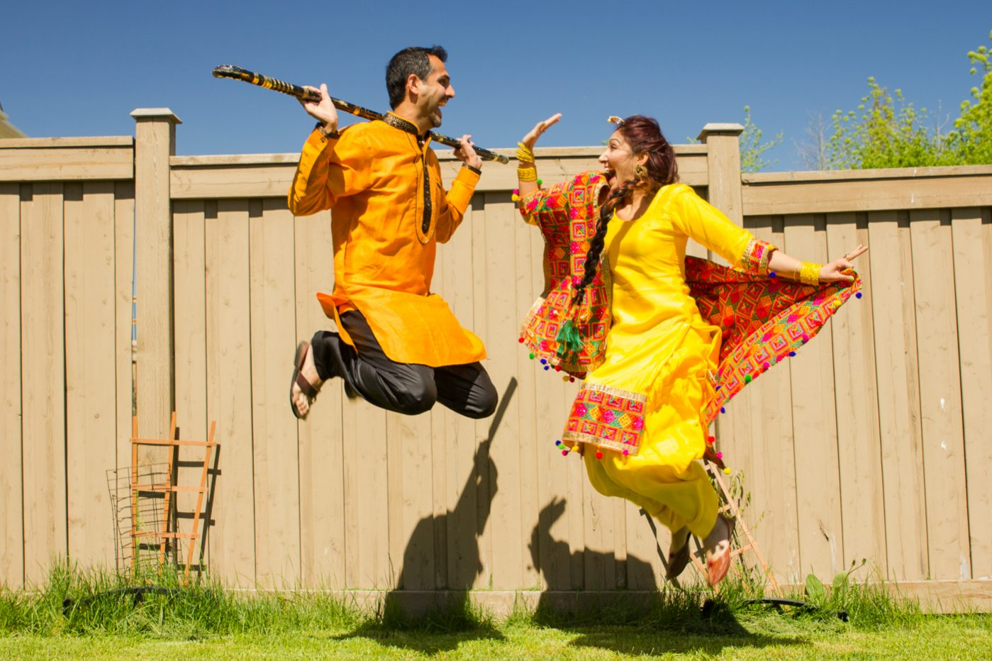 Punjabi dressed couple jumping in bhangra dance.