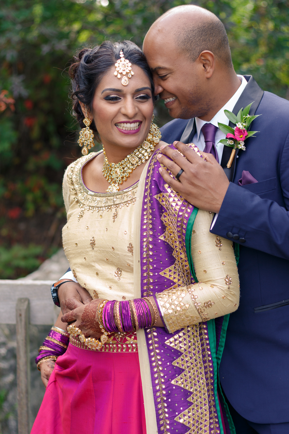 Happy South Asian bride and groom with groom's hand on bride's shoulder.