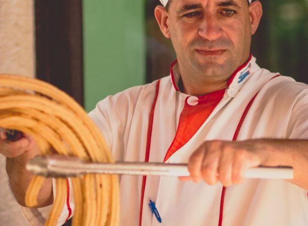Street photography of churro maker in Cuba.