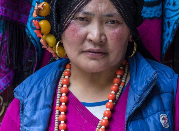 Travel portrait of Tibetan woman in Jiuzhaigou, China.