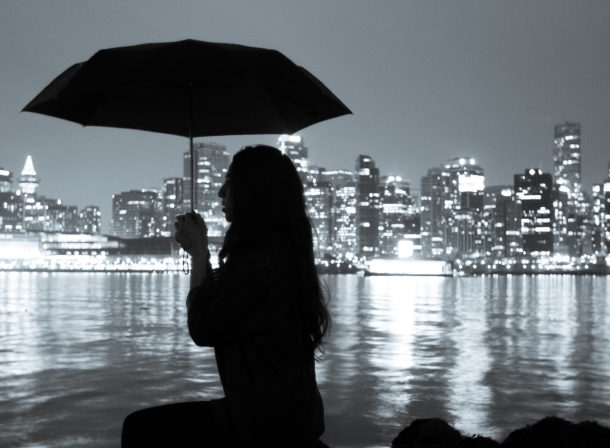 Girl holding umbrella. Silhouette in Stanley Park, overlooking Vancouver skyline.