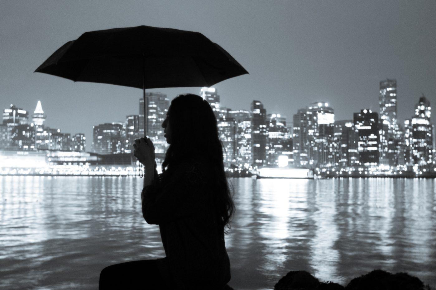 Girl holding umbrella. Silhouette in Stanley Park, overlooking Vancouver skyline.