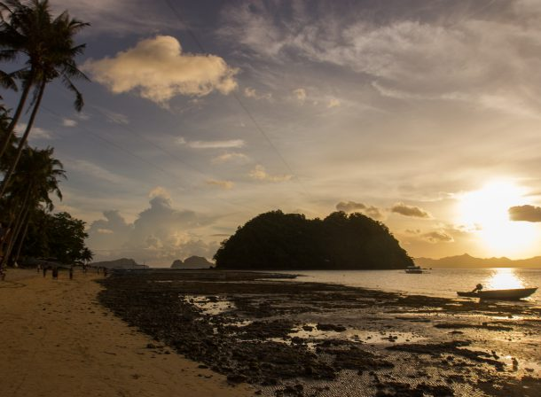 Sunset travel photography in El Nido, Palawan, Philippines. Silhouettes of islands, palm trees, and boats.
