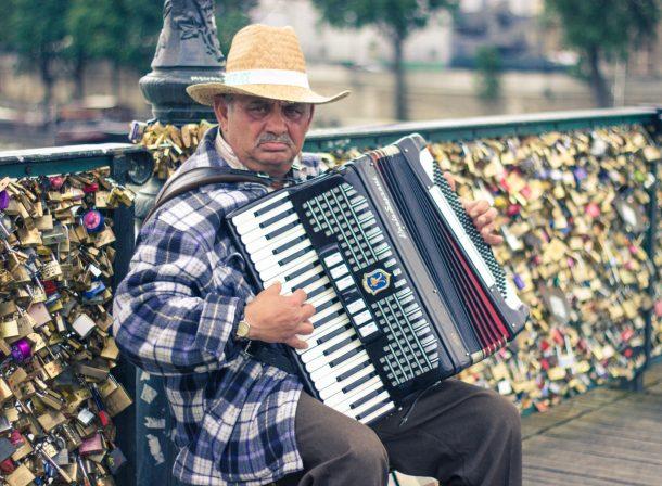 Street photography Harmonium busker on the Love Locks Bridge in Paris, France.
