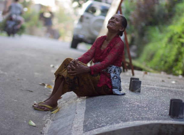 Street photography. Woman on street curb laughing in Bali, Indonesia.