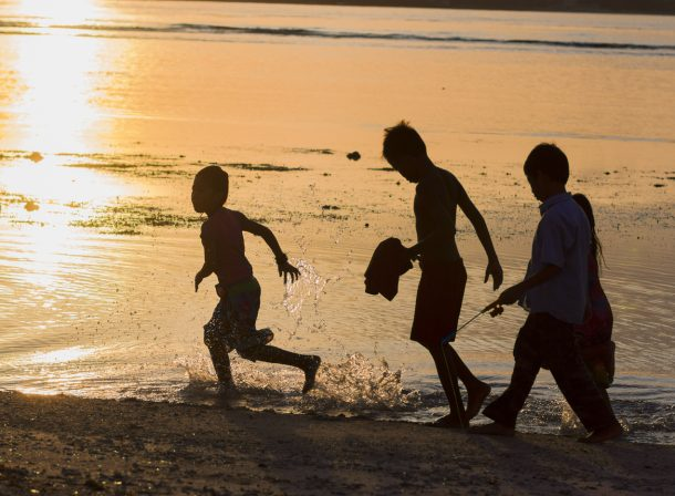 Street photography. Silhouettes of kids playing on the beach in El Nido, Palawan, Philippines.