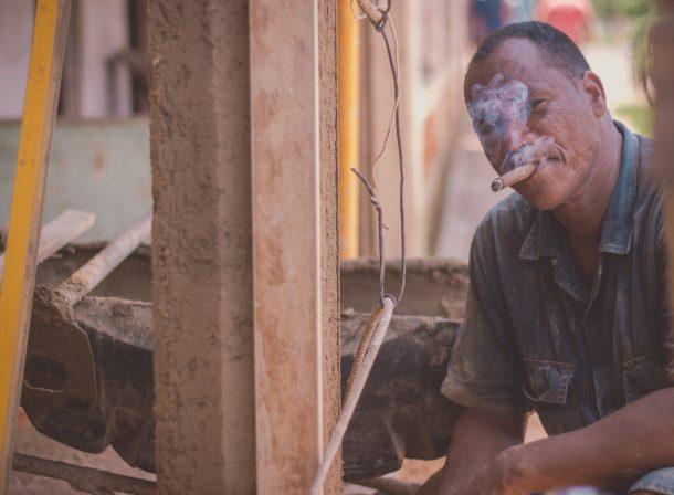 Travel photography. Portrait of man on the street in Havana, Cuba, having a smoke.