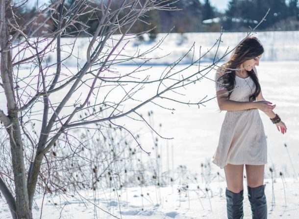 Girl standing in white dress in the snow, full Canadian winter.