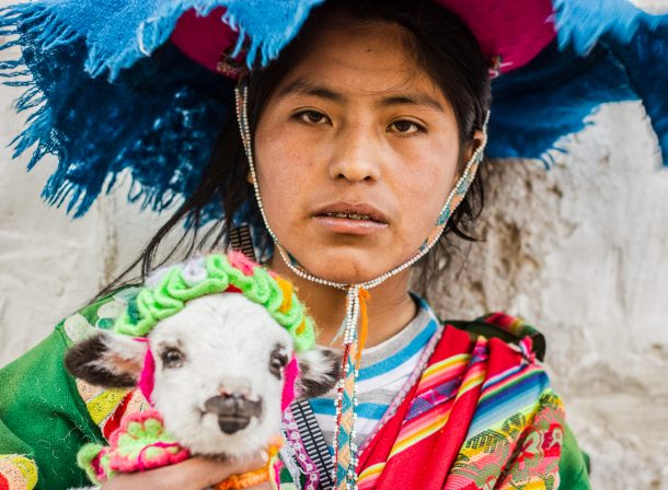 Street portrait of woman in Arequipa, Peru, dressed in Incan cultural wear with her pet lamb. Travel photography.