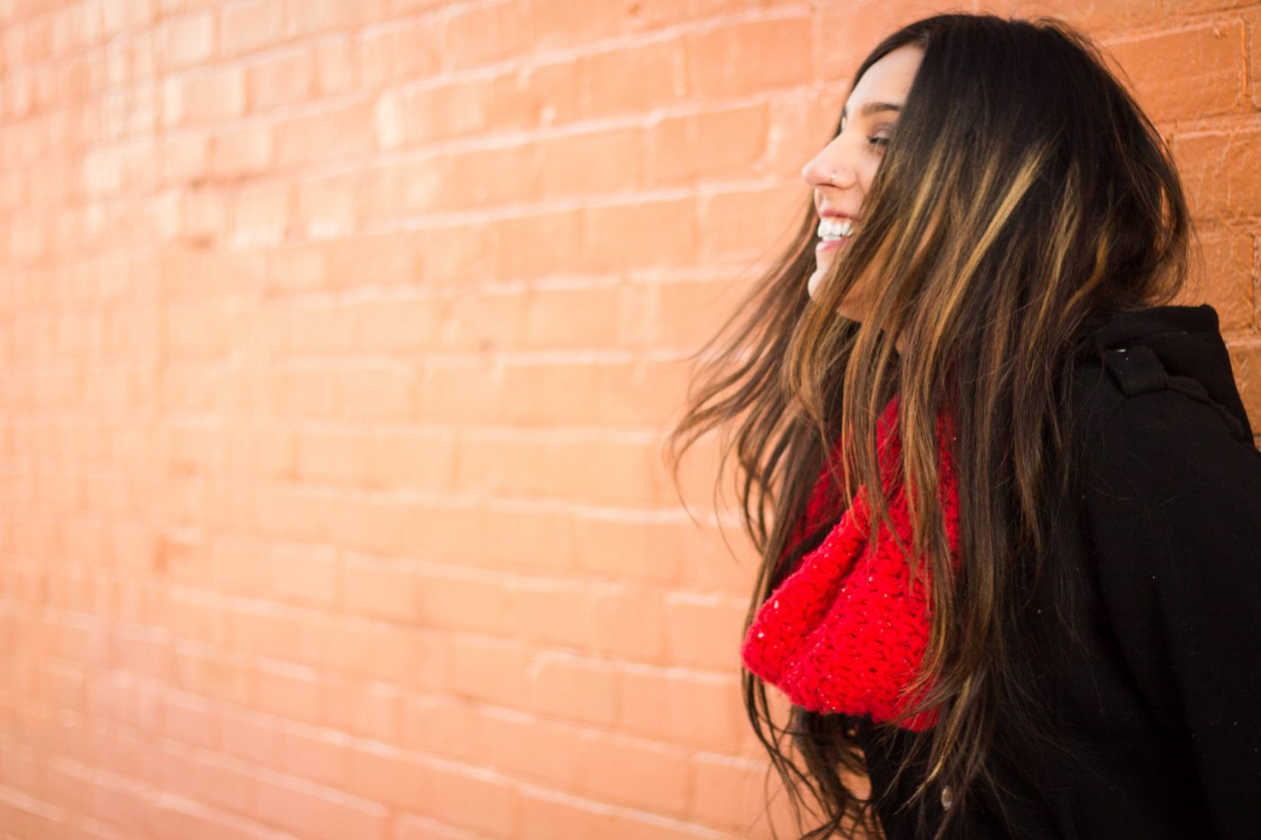 Girl laughing, wearing black coat and red scarf.
