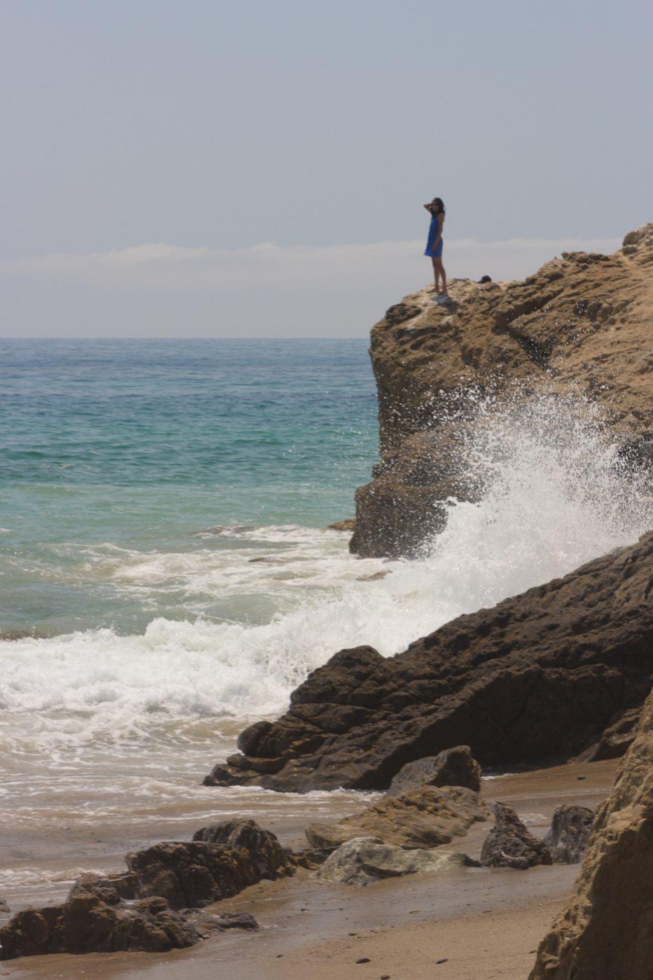 Malibu surroundings, girl looking over the water with wave crashing