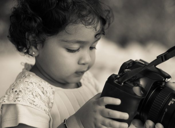 Antique light on a toddler girl with Canon camera in hand.