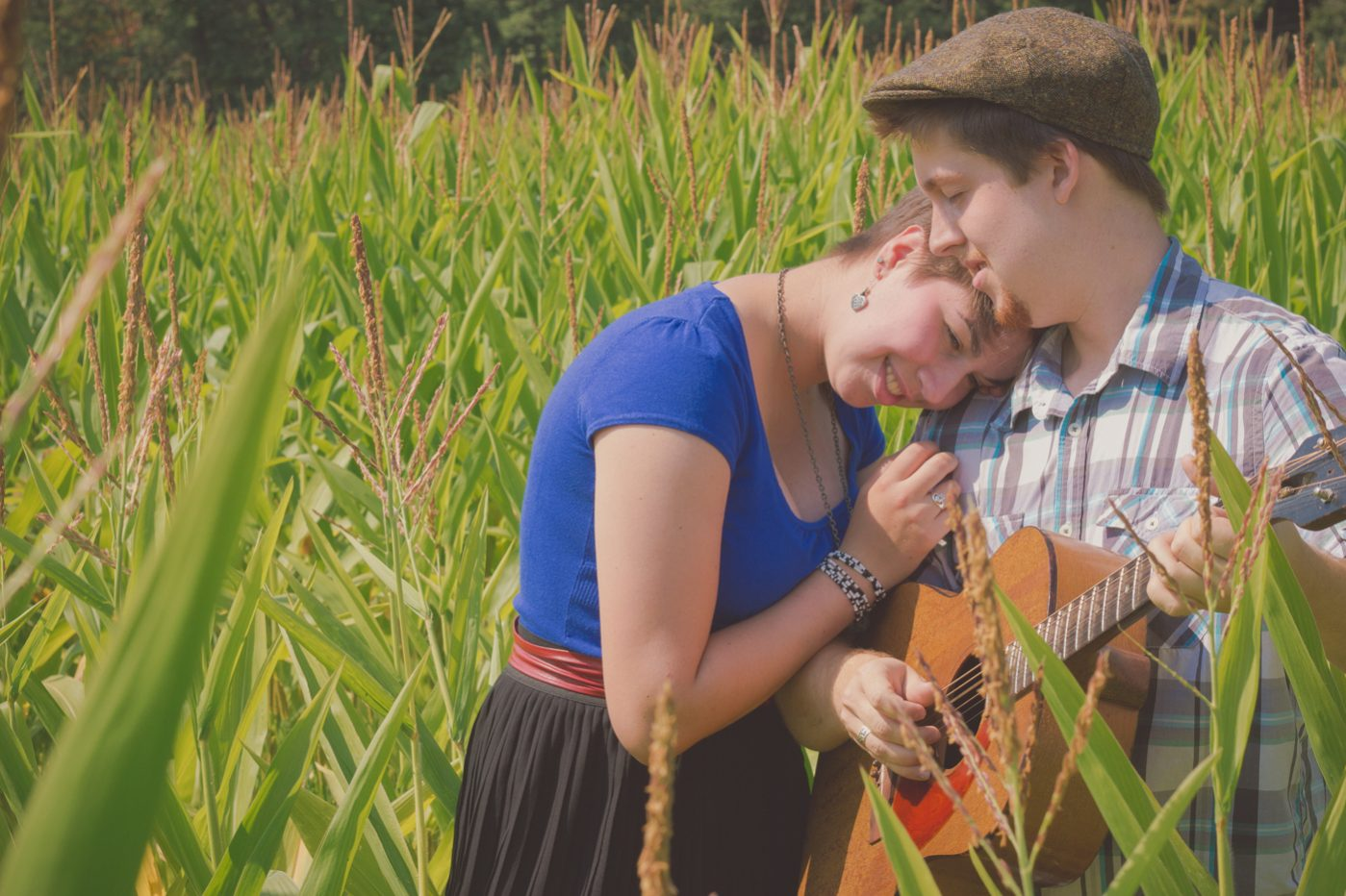 Couple playing guitar in a corn field.