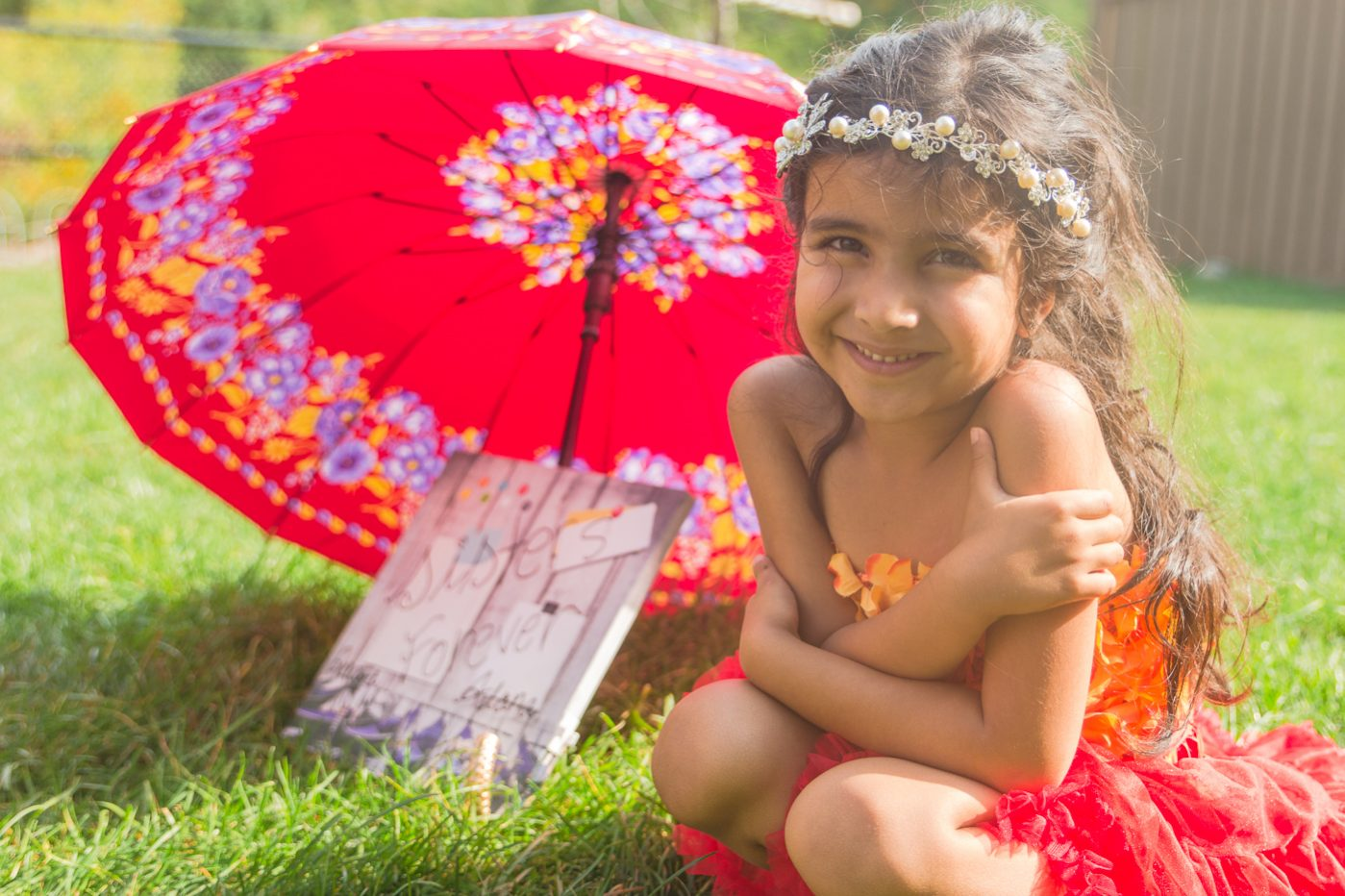 Girl in red dress with matching red umbrella in sunlight.