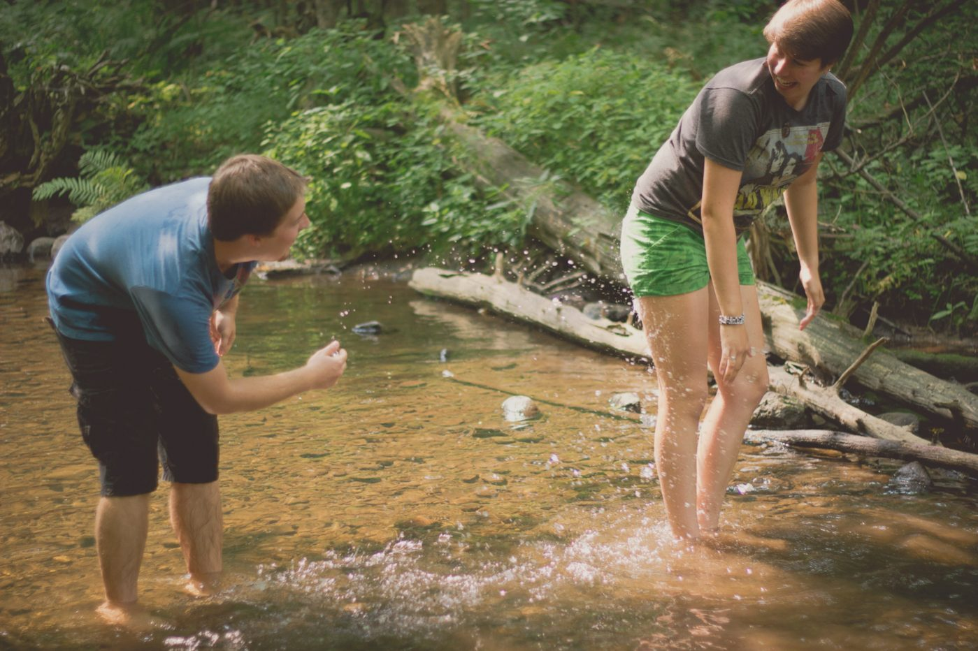 Couple playing with the water in a small creek.