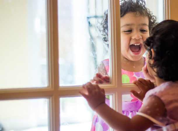 Toddler twins facing each other through a window-door.