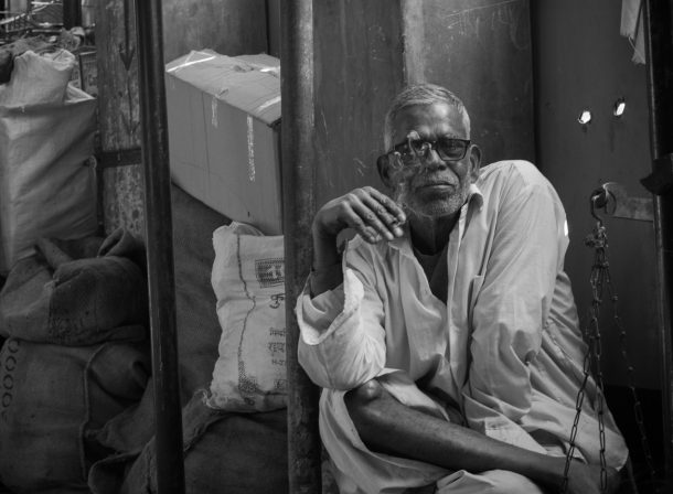 Man posing with his cigarette near Crawford Market, Mumbai, India. Black and white travel street photography.