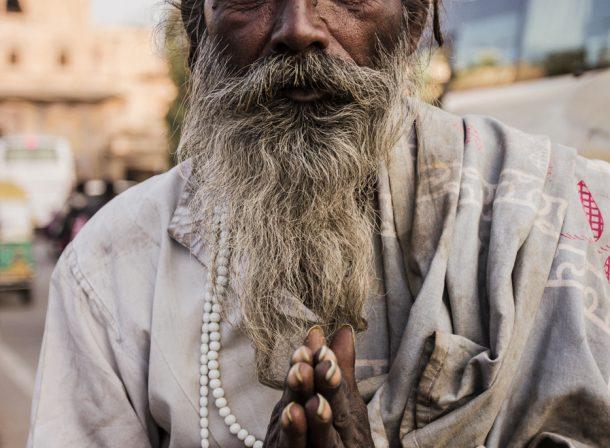Elder homeless man folding his hands, asking for support.