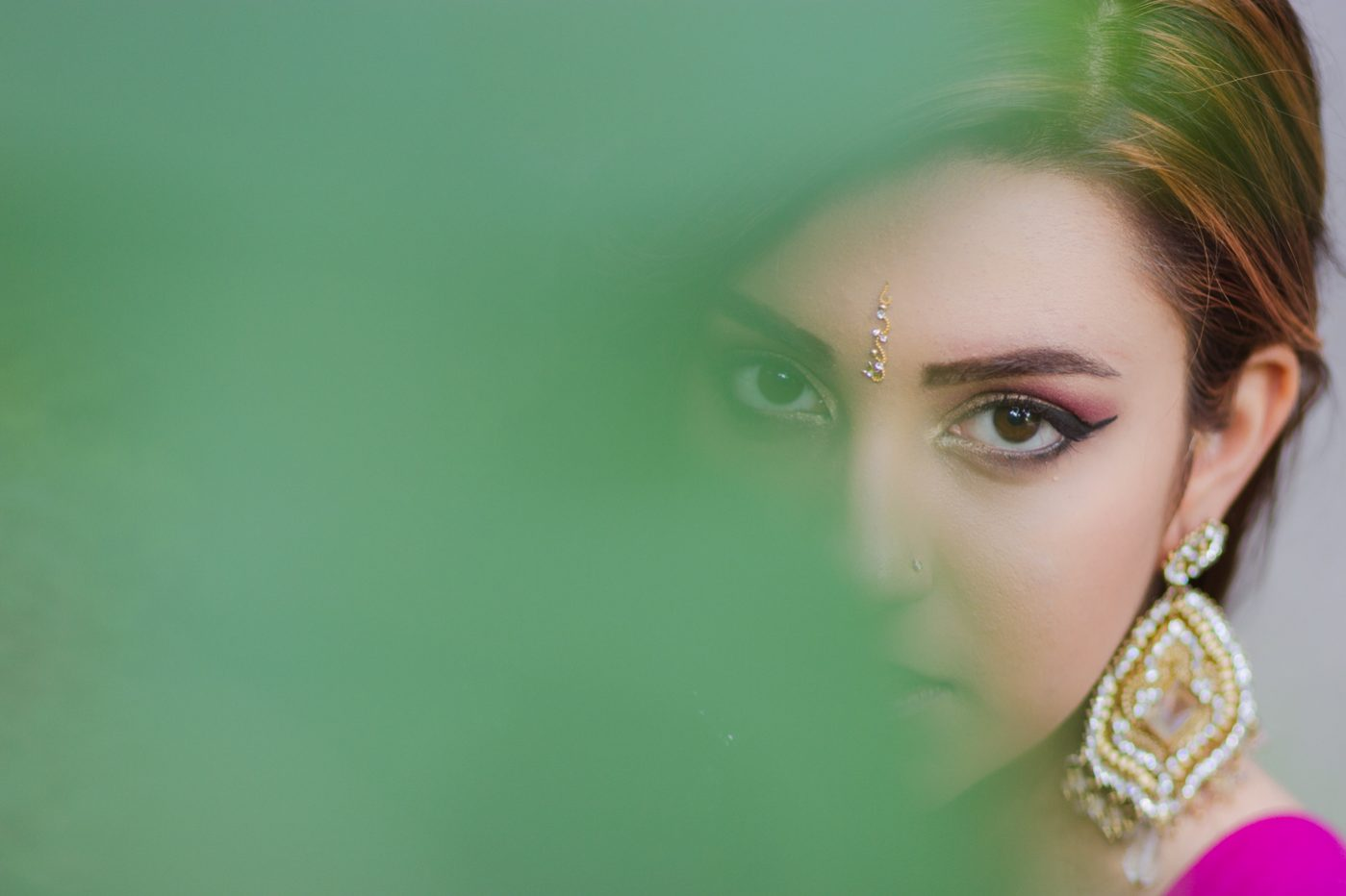 Eyes behind the edge of a lead. Indian girl in lehnga.