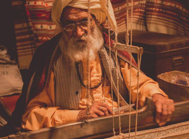 Old man weaving a quilt at Rangla Punjab, Jalandhar, India.