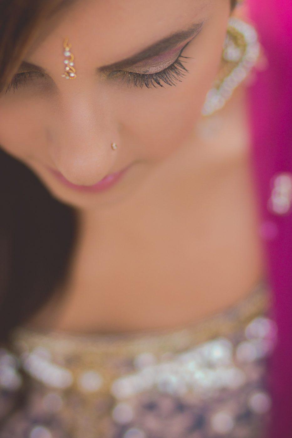 Portrait session focused on girl's eyelashes with lehnga details in bokeh.