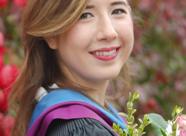 Portrait of girl in graduation outfit and flowers.