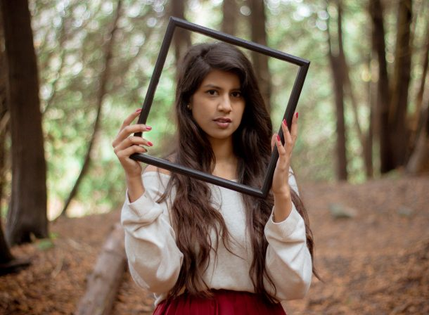 Girl holding picture frame in forest.
