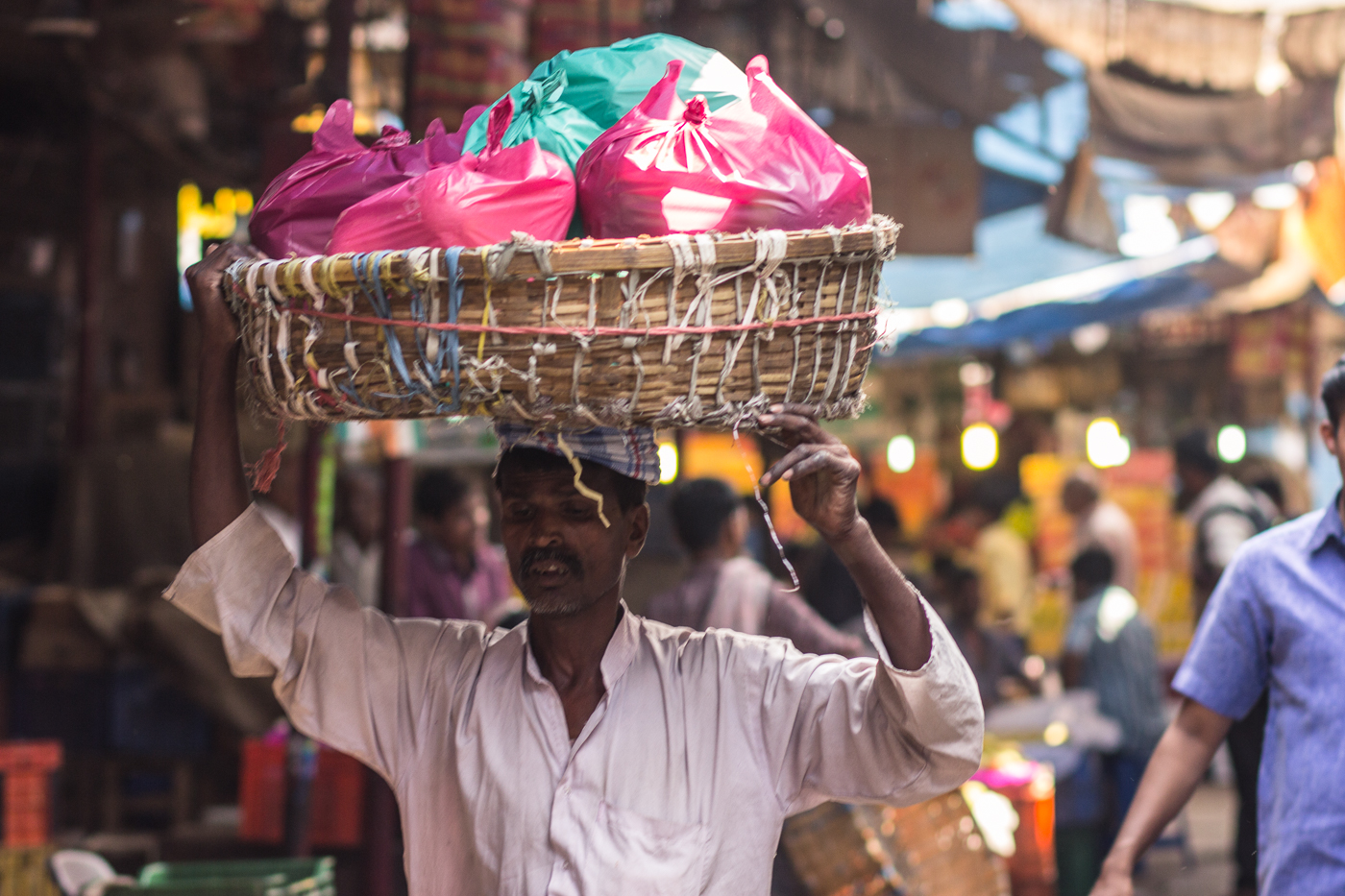 Vendor holding a basket of goods above his head in Crawford Market, Mumbai, Maharashtra, India. Travel street photography.