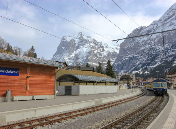 Grindelwald train station in Switzerland against a beautiful background of the Swiss Alps.
