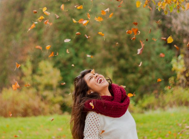 Girl laughing while leaves fall on her.