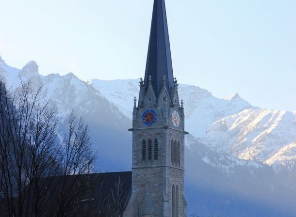 Liechtenstein Vaduz Cathedral in Europe with snowy mountains in the back. Travel landscape photography.