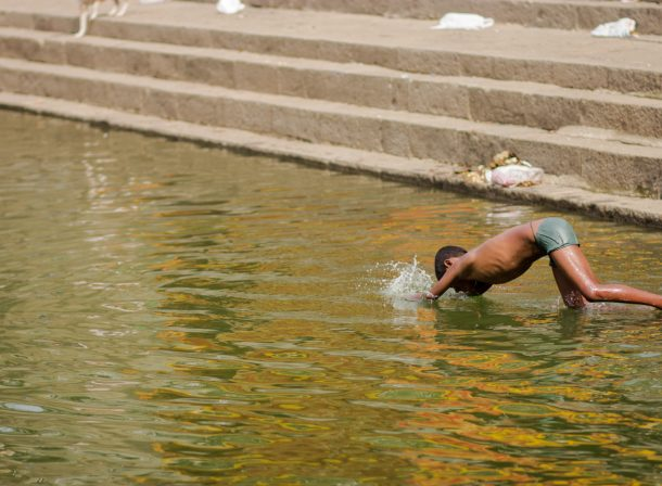 Boy jumping into a ghat in Mumbai.