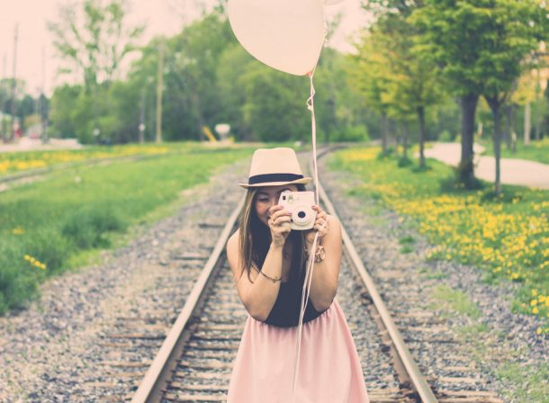 Girl standing on train tracks holding Polaroid camera with balloons.