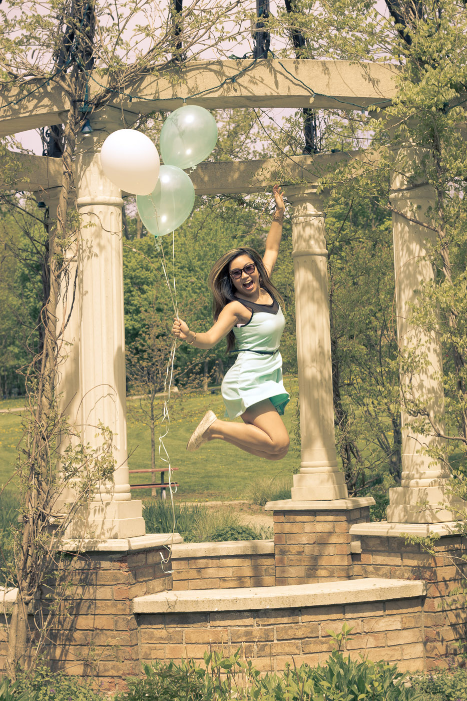 Girl holding balloons jumping with joy in an outdoor vine-covered gazebo.