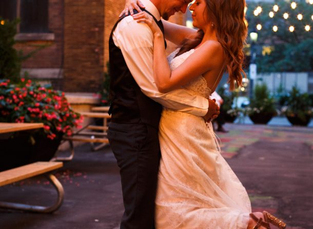 Bride and groom in each other's arms standing under string lights in a graffiti alley just after their wedding ceremony.